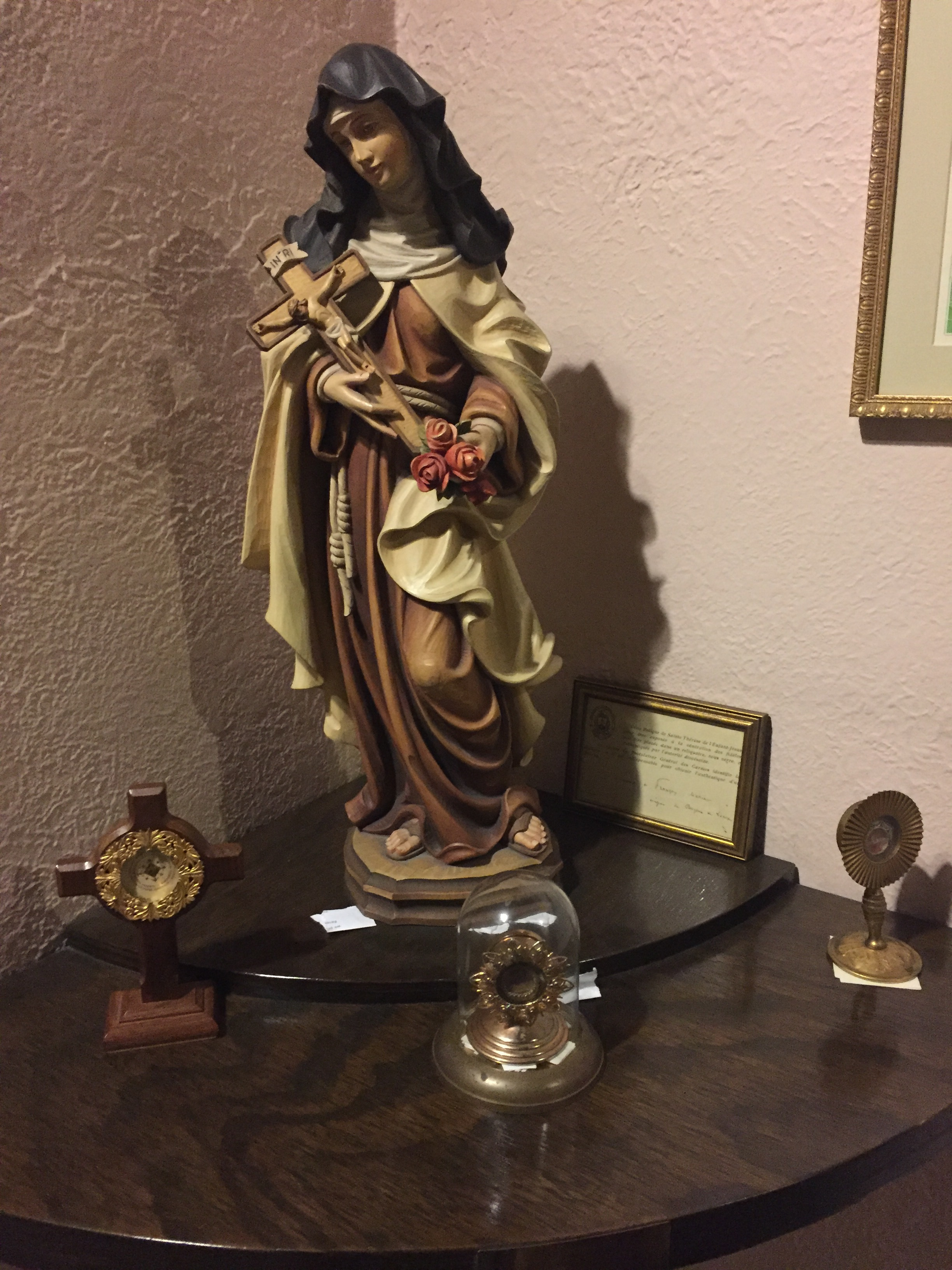 A statue of St. Therese. The three items in the foreground are relics from St. Therese.