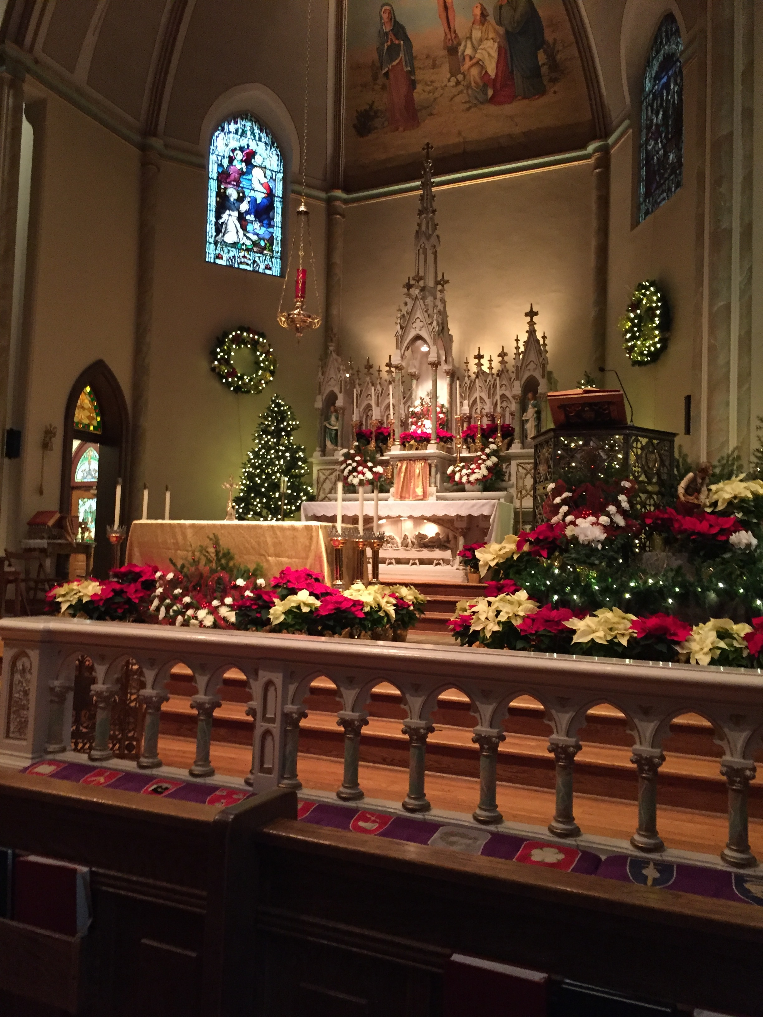The altar, and yes, we USE those communion rails! The kneeler pads were embroidered by members of the altar guild, I believe. The stained glass window you can see is of St. Dominic receiving the rosary from Our Lady.