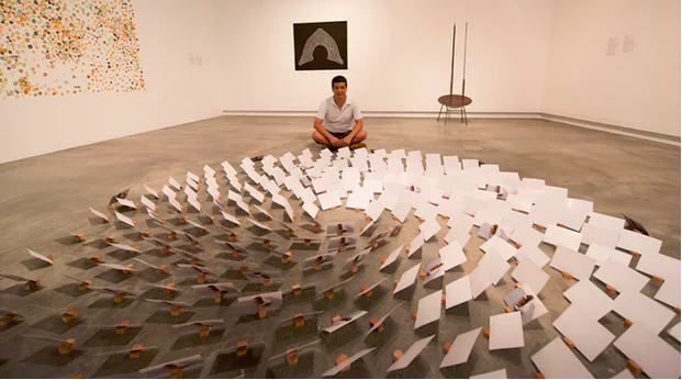Hazara refugee Sha Sarwari with his floor-based installation Silent Conversation, featuring 1,975 blank postcards. Photograph: Michael Cranfield