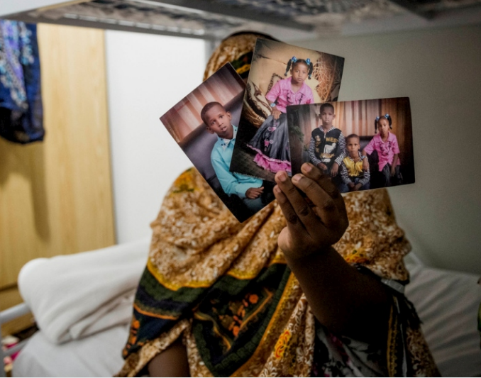 Somali refugee Sabah holds up photos of her three children at a detention centre in Nauru, in 2014. Sabah, 28, had not seen her children since they became separated fleeing extremist violence in Somalia three years earlier.   © Panos/ Vlad Sokhin