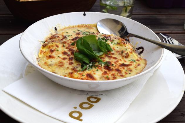 Mit Steinpilzen gefüllte Pasta in Eierschwammerlsoße und überbackenem Käse