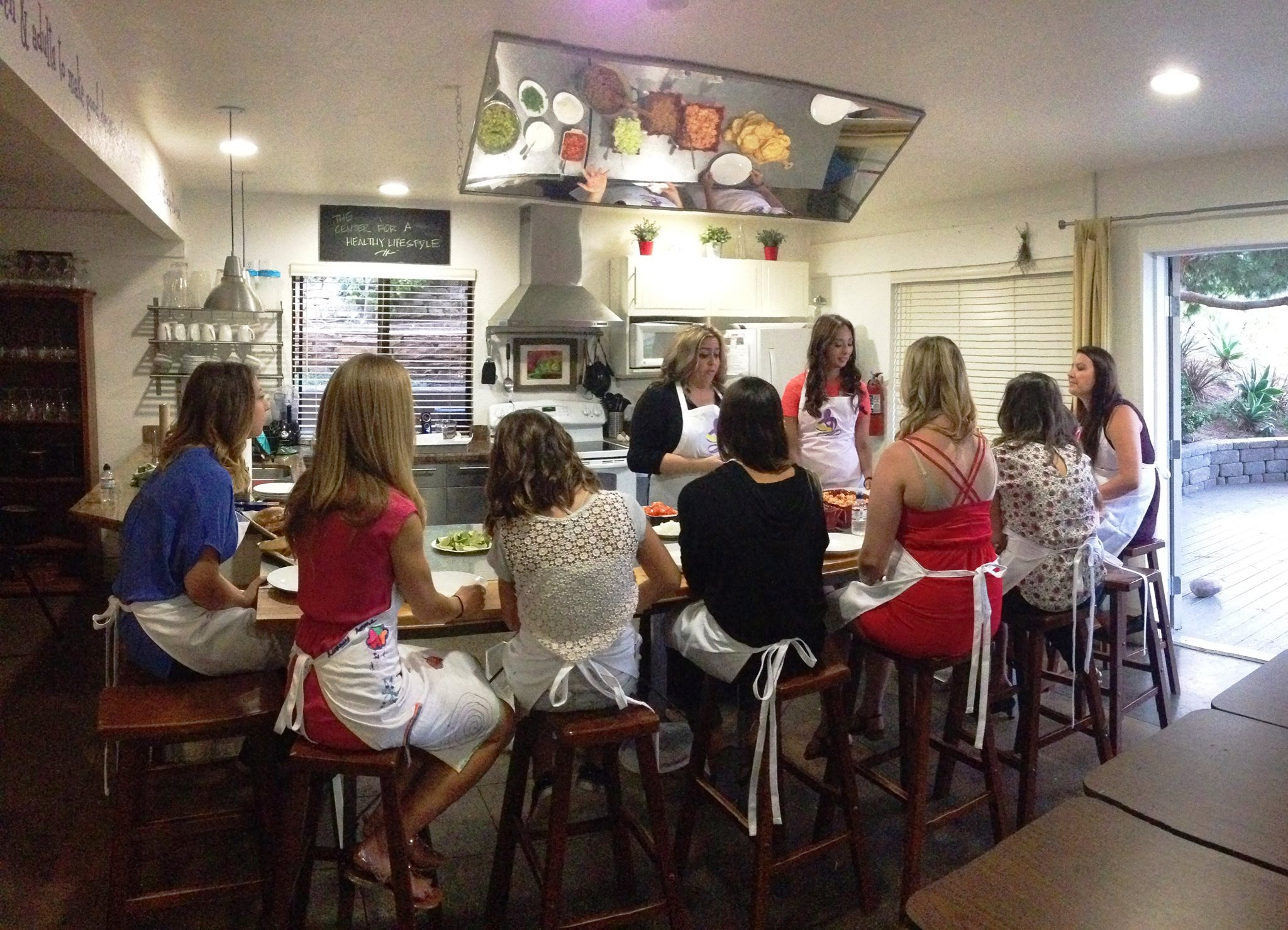 Chula's Mission founders Mayra San Juan and Lyndsey Ruiz work with mentees in the kitchen.