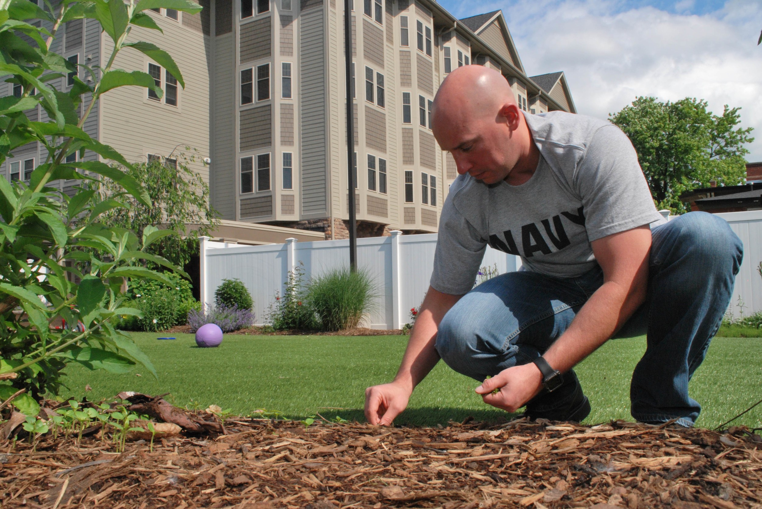 SYRACUSE, N.Y. (June 6, 2016) Machinist Mate (Auxiliary) 1st Class (SS) Joel L. Towry, assigned to the Los Angeles-class attack submarine USS Albany (SSN 753), pulls weeds during a community relations event at Ronald McDonald House Central New York. This is one of several community relations events planned as part of Navy Week Syracuse. (U.S. Navy photo by Mass Communication Specialist 2nd Class Adam D. Wainwright/Released)