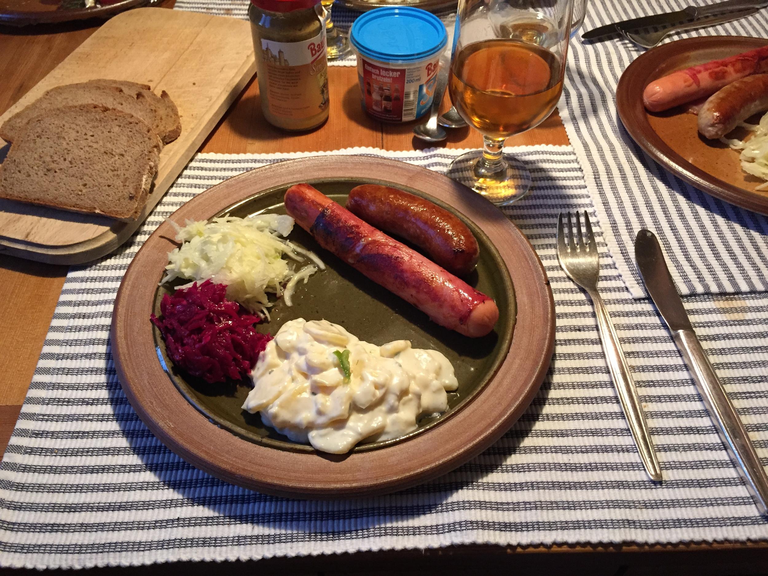 Wurst, Kartoffelsalat, Rotkohl und Sauerkraut