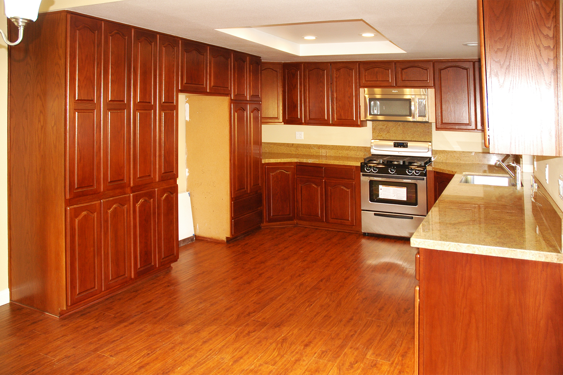 After Kitchen in Agoura Hills with new floors, stained cabinets counters and appliances.