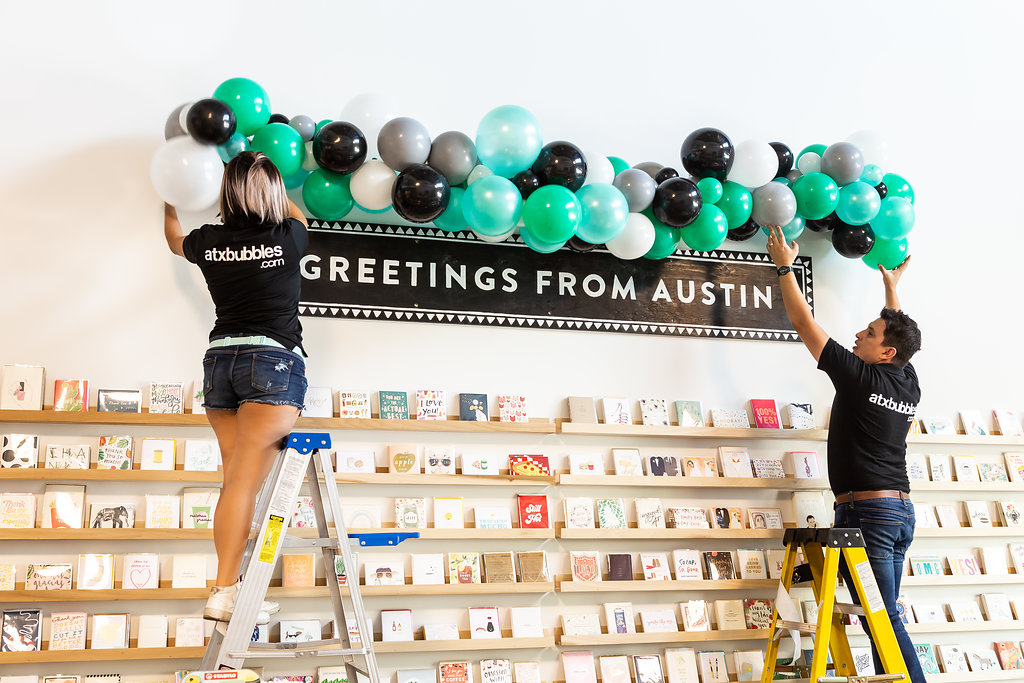 ATX BUBBLES installing a balloon garland at The Paper + Craft Pantry Re-Opening Party.