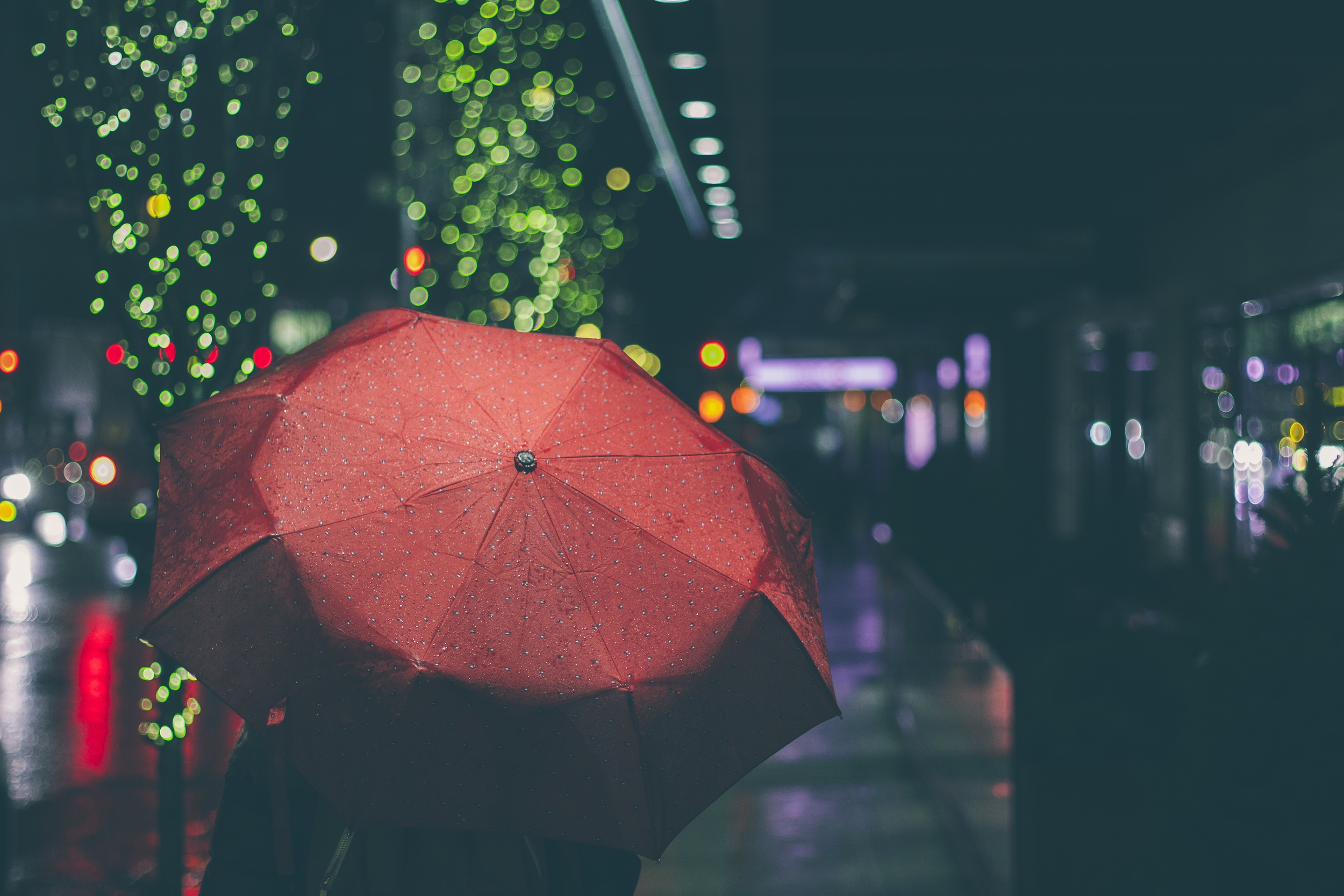 Picture of person with red umbrella walking down a nighttime city street lit with twinkle lights