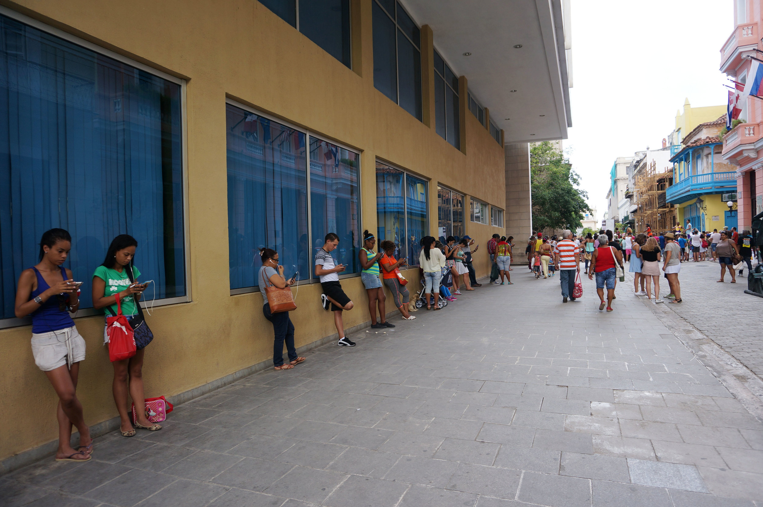 Lined up along a building on Obispo Street using the wifi.