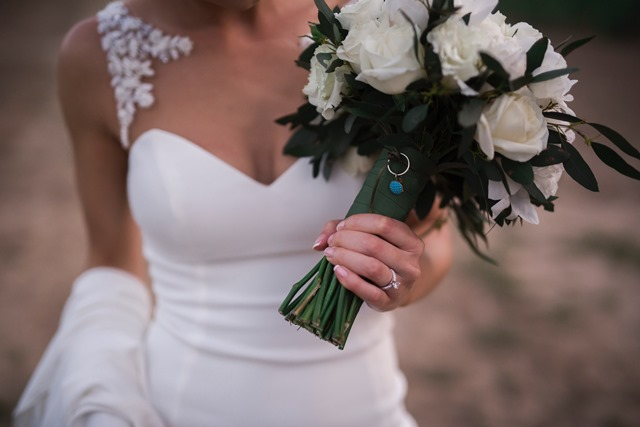This photo of my bouquet has my grandma's earring who has passed away and my mum's original wedding ring so they were together and with me walking down the aisle. These precious family inclusions also formed part of my 'something borrowed, old and blue'.