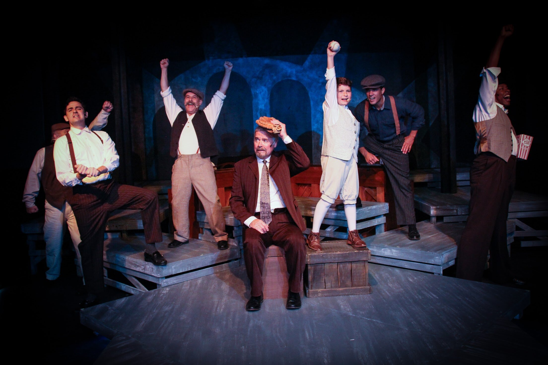 Father (Dennis Holland), seated, and his son (Ari Zimmer) and the male cast of  Ragtime