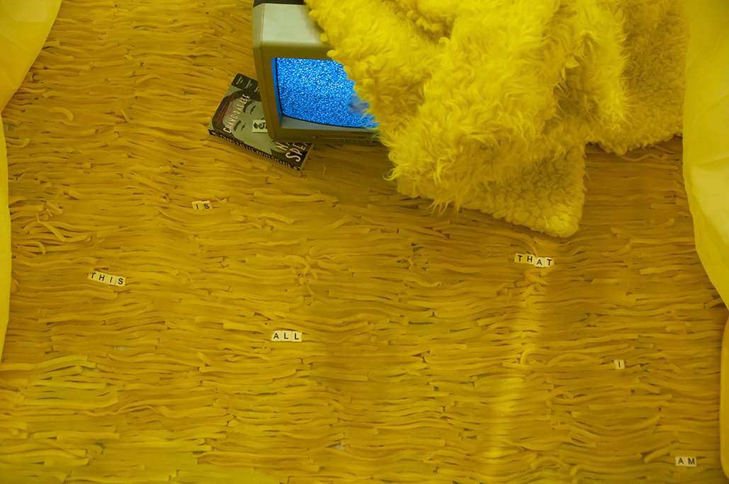 "Is this | This is…  Multimedia installation: yellow curtains, old television, copy of Native Speaker by Chang Rae Lee, wig, 20 packs of rectangle dan moo ji, 5 packs of circle dan moo ji, print, shag rug, scrabble letters.  120"" x 240"" x 240""  Installation view."