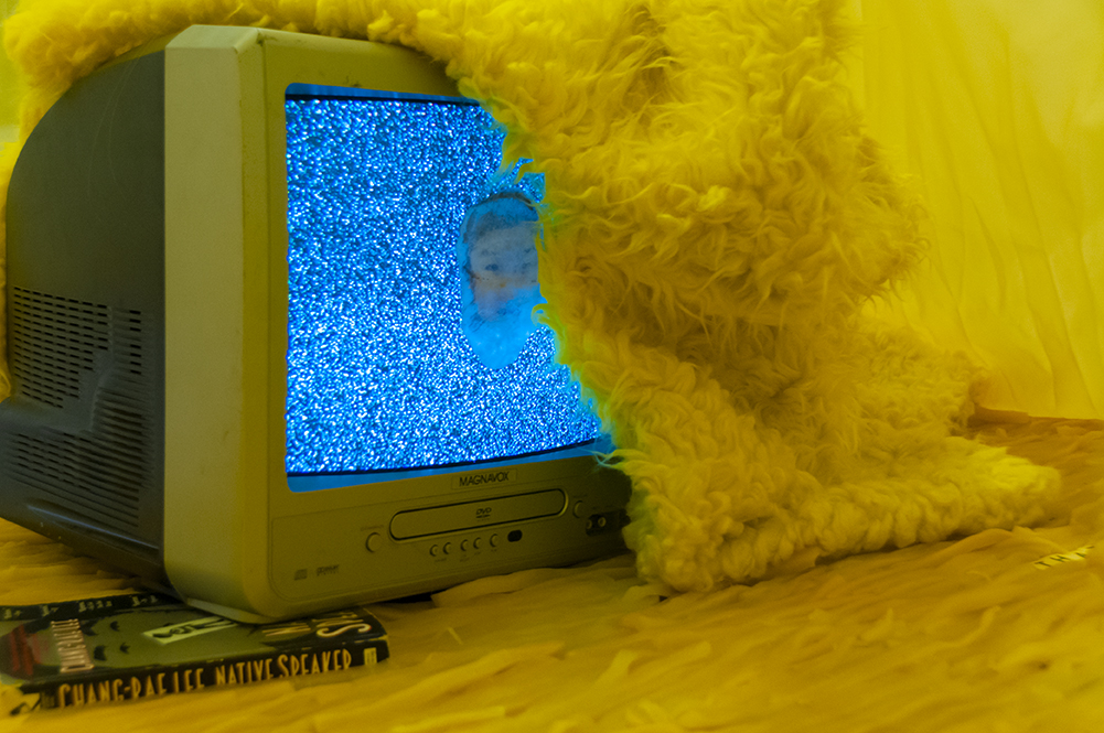 "Is this | This is…  Multimedia installation: yellow curtains, old television, copy of Native Speaker by Chang Rae Lee, wig, 20 packs of rectangle dan moo ji, 5 packs of circle dan moo ji, print, shag rug, scrabble letters.  120"" x 240"" x 240""  Detail."