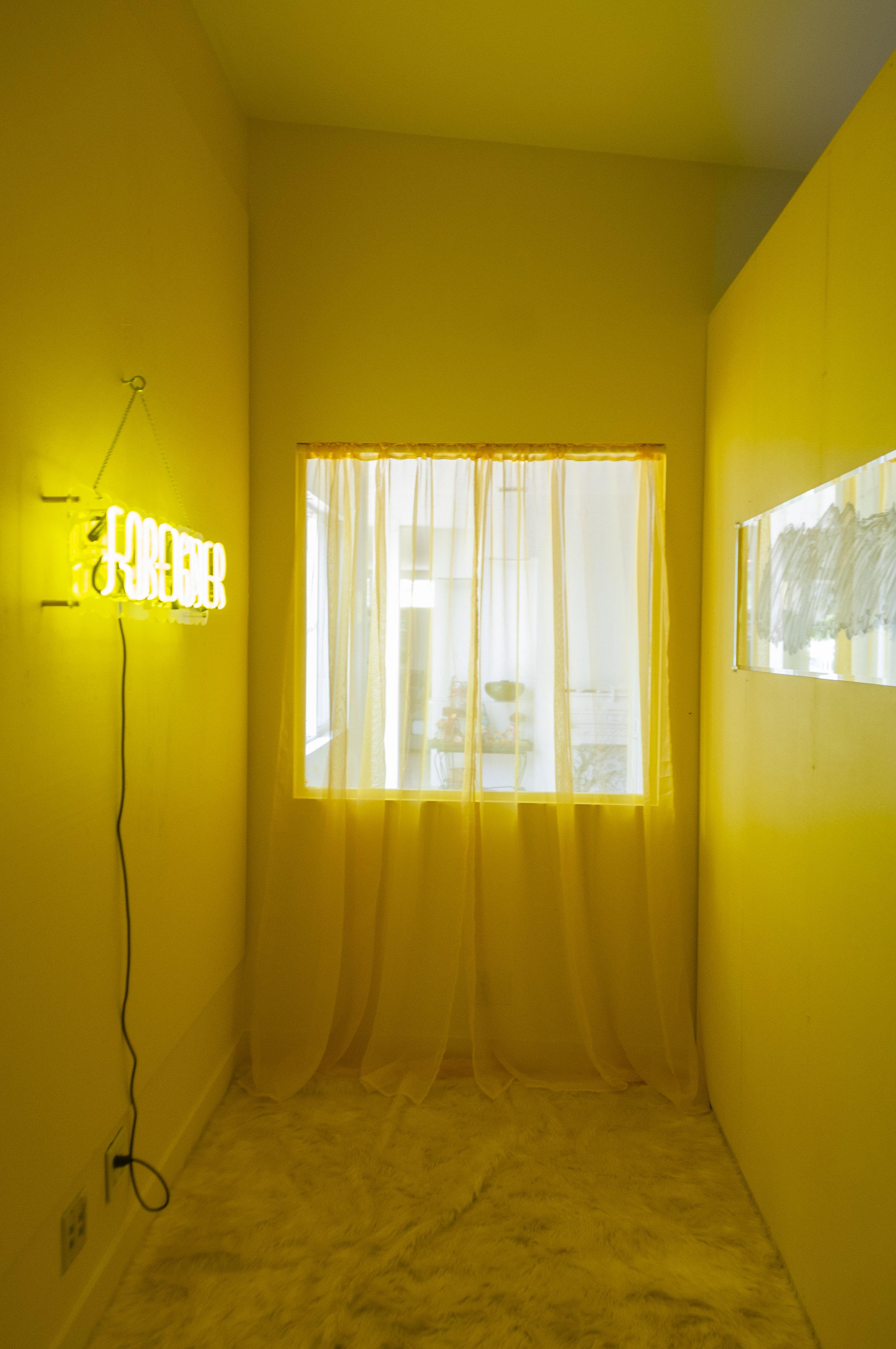 "Koreatown Comfort  Multimedia installation: yellow paint, FOREIGNER custom neon sign, mirror, acrylic paint, yellow curtains, shag rug, custom made stud wall.   180"" x 84"" x 96""   Installation view."