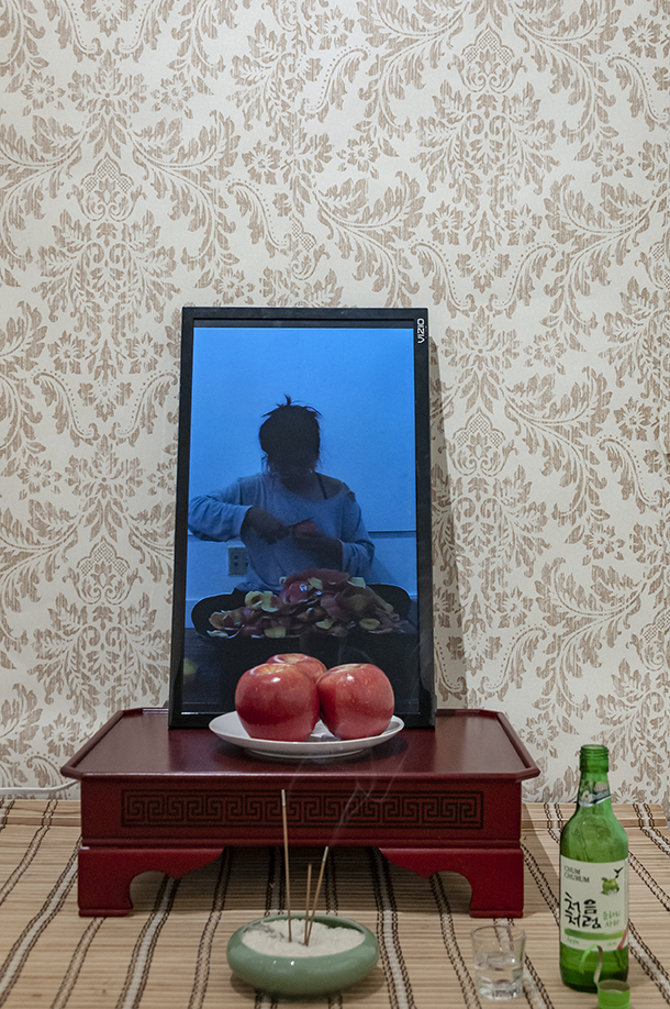 Mom, I can get married now!  Installation: performance documentation, apple soju, soju glass, incense, rice, incense holder, apples, ceramic plate, bamboo curtain, 밥상, wallpaper.  Installation view.