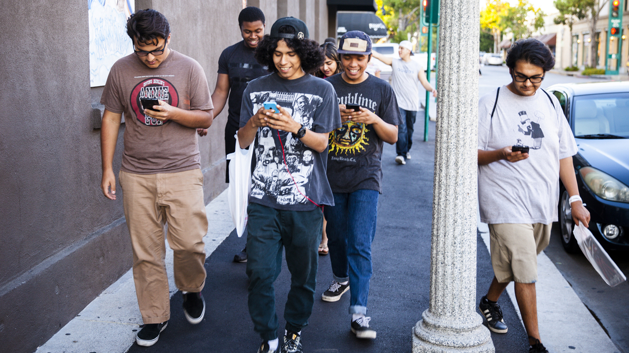 Pedesterians on their phones / Photo via tonsofbuzz.com