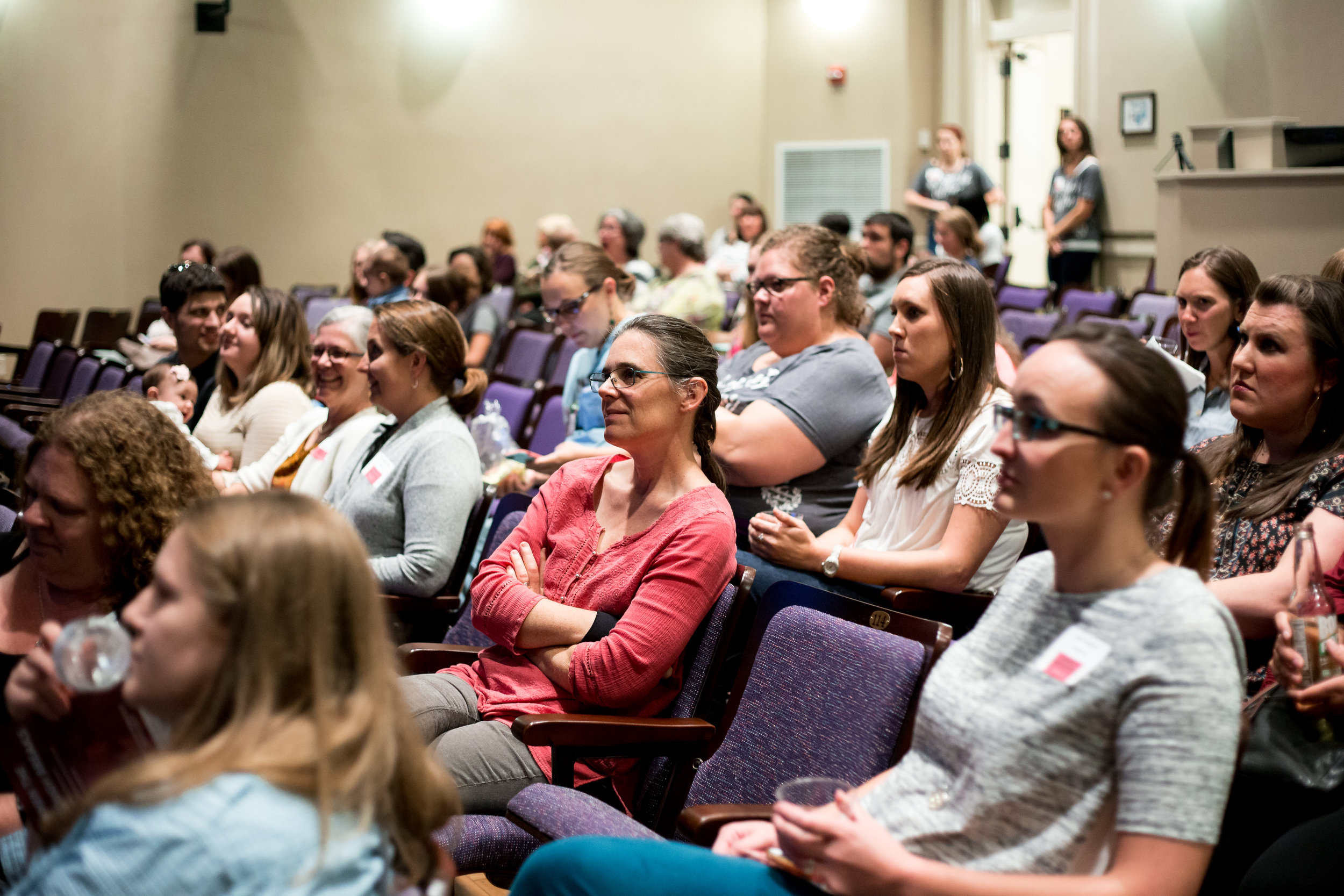 Community partners, Ashley Graham LCSW, Leslie Payne CPM, Erin Baird CNM, Lisa Neumann CNM , Amy Rugh LPC, Katie Page CNM, and more sit among brave men and women while volunteer staff lovingly watch over the crowd. © Christi Stafford Photography