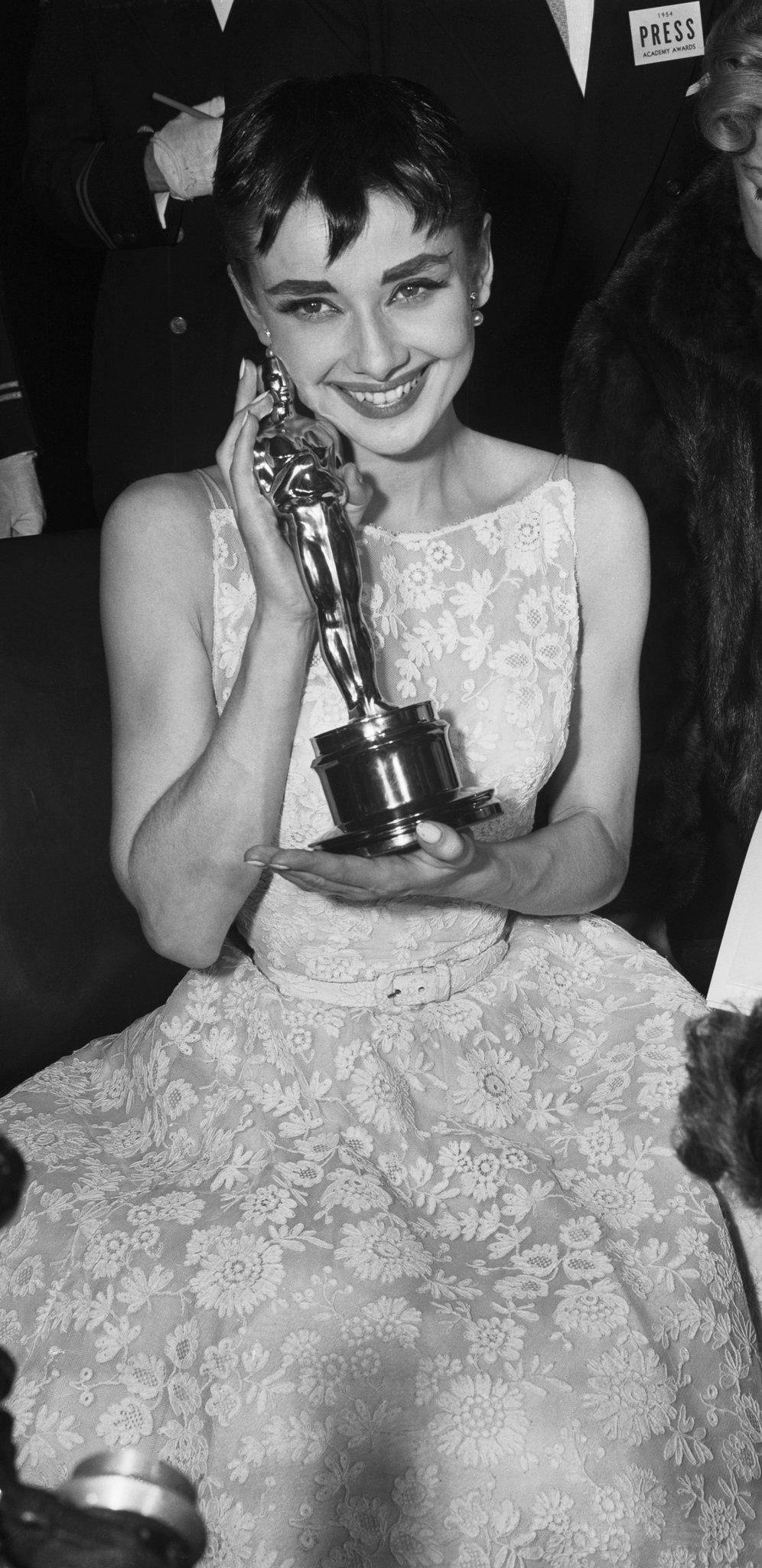 """Ms. Hepburn wearing Givenchy at the 1954 Academy Awards where she received the Best Actress Oscar for """"Roman Holiday.""""CreditBettmann/Getty Images"""