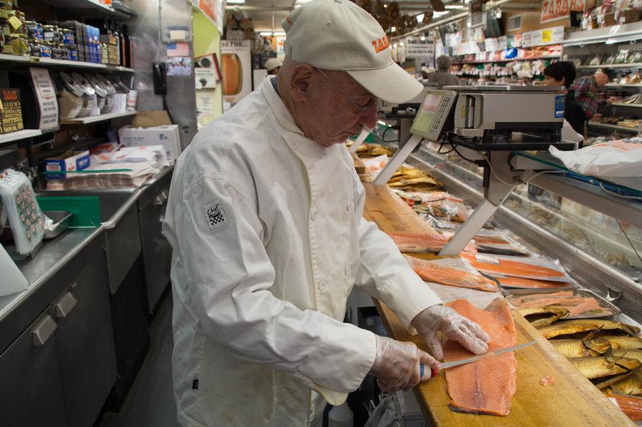 Len Berk slices salmon at Zabar's Food Emporium. (npr.org)
