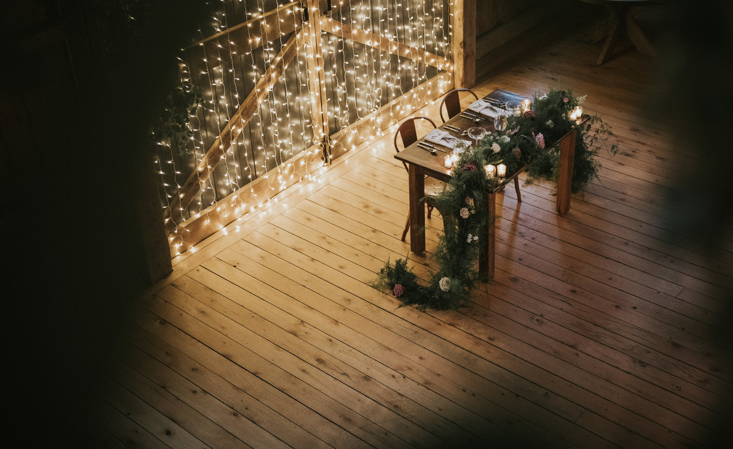 Flanagan farm maine wedding barn sweetheart table lights greens garland.jpg