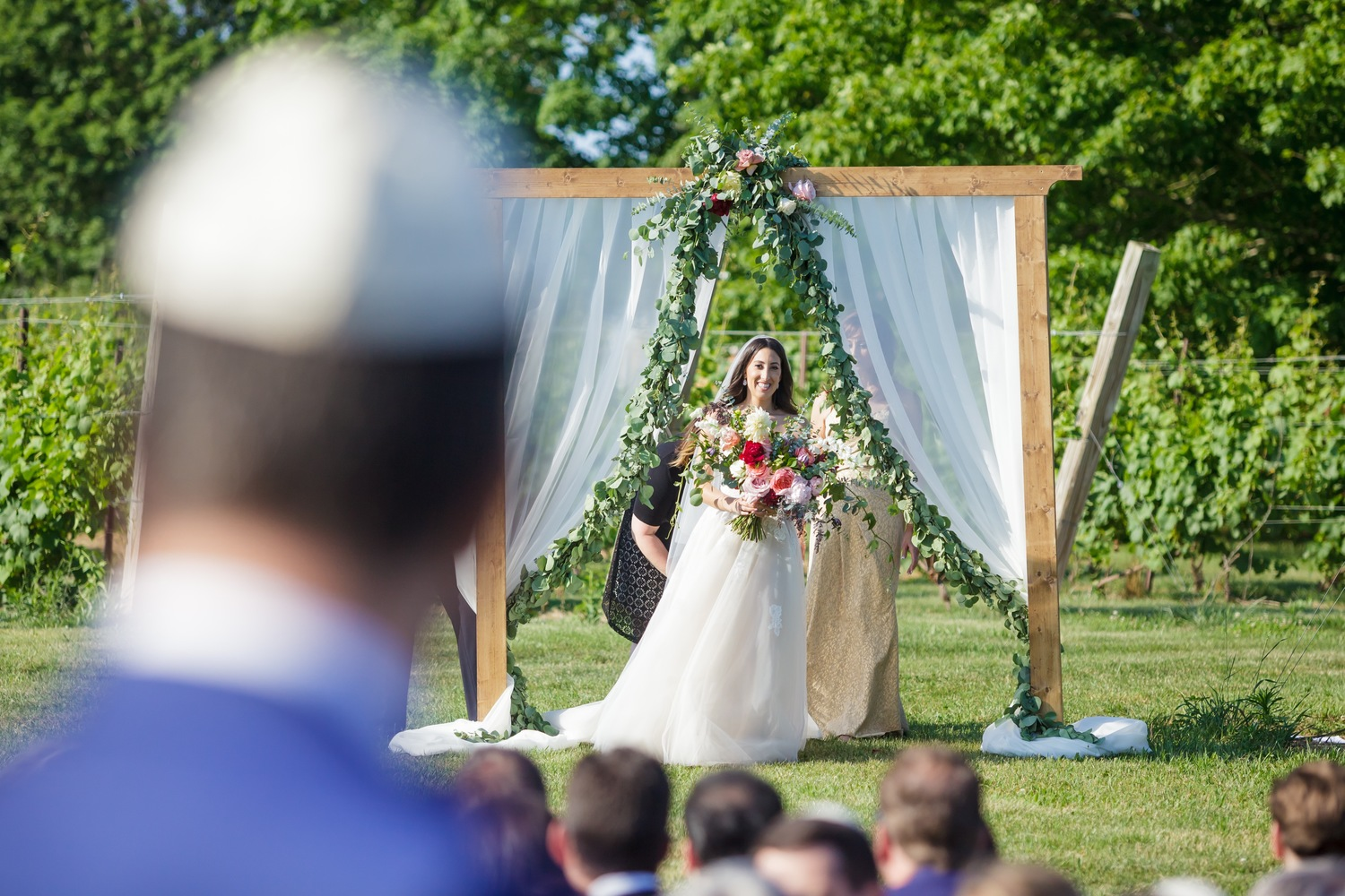 Preston Ridge Vineyard wedding bride bridal bouquet ceremony arbor green garland.jpg