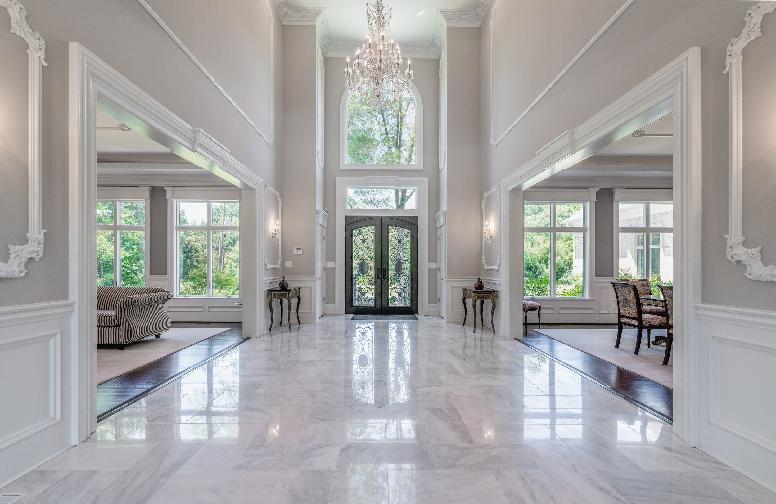 Two-story Entry Foyer features marble flooring and elegant crown moldings