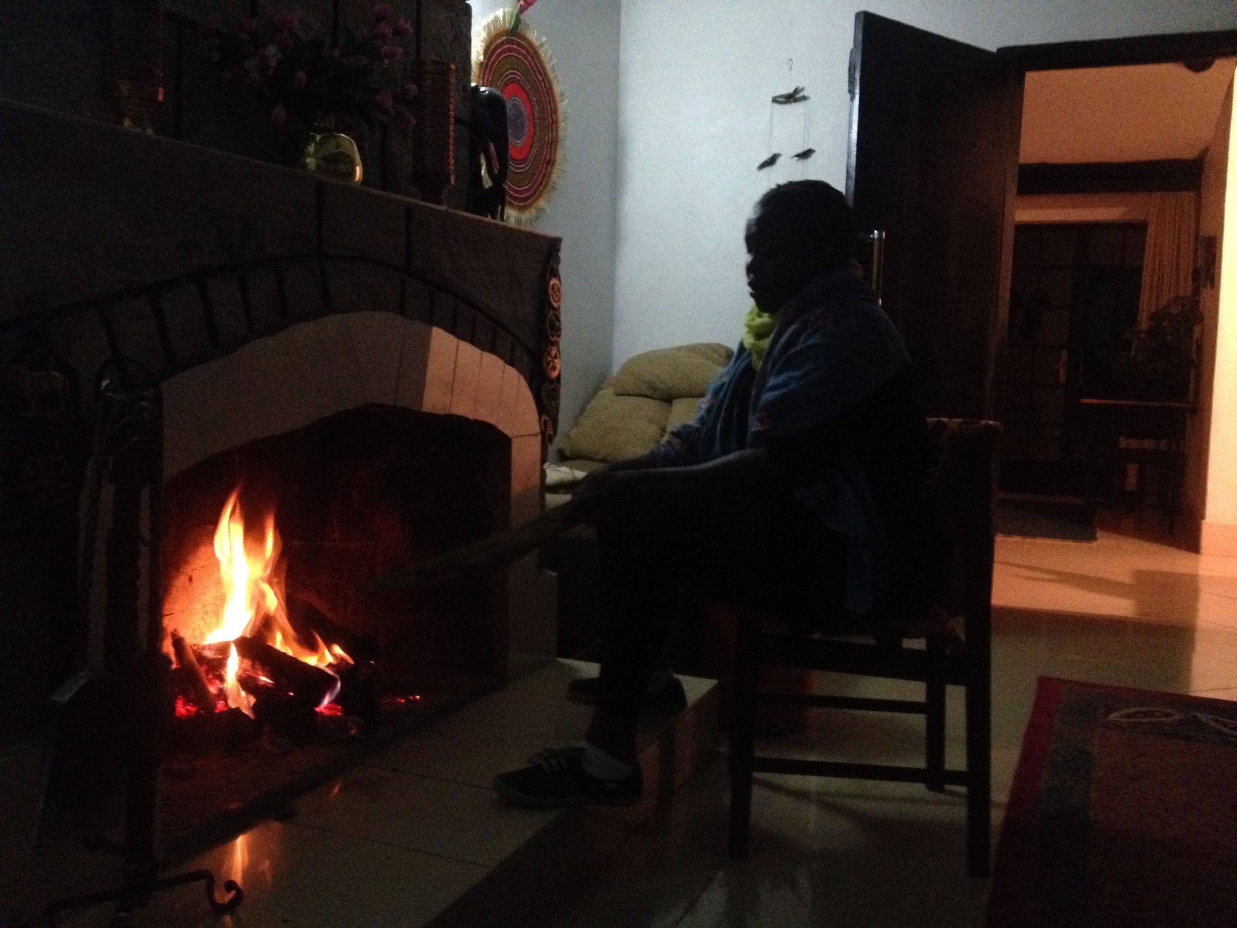 Martha sits in front of the fire at the B&B in Naivasha.