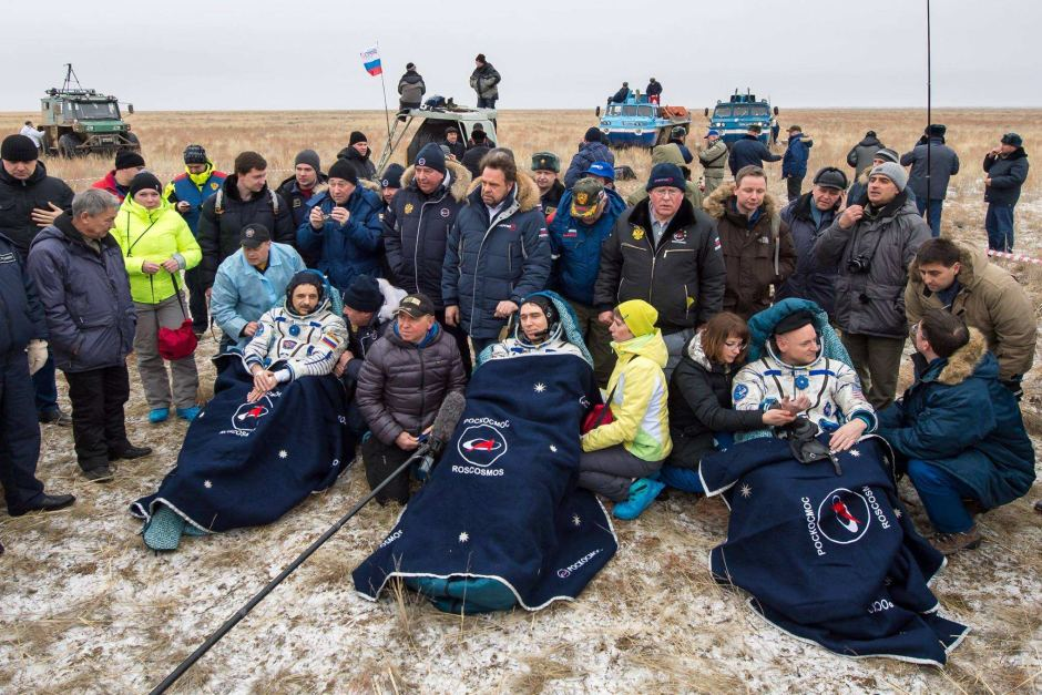 Russian cosmonauts Mikhail Kornienko (left), Sergey Volkov of Roscosmos (center), and Astronaut Scott Kelly rest in chairs outside their Soyuz TMA-18M spacecraft. Photo Credit: NASA/Bill Ingalls