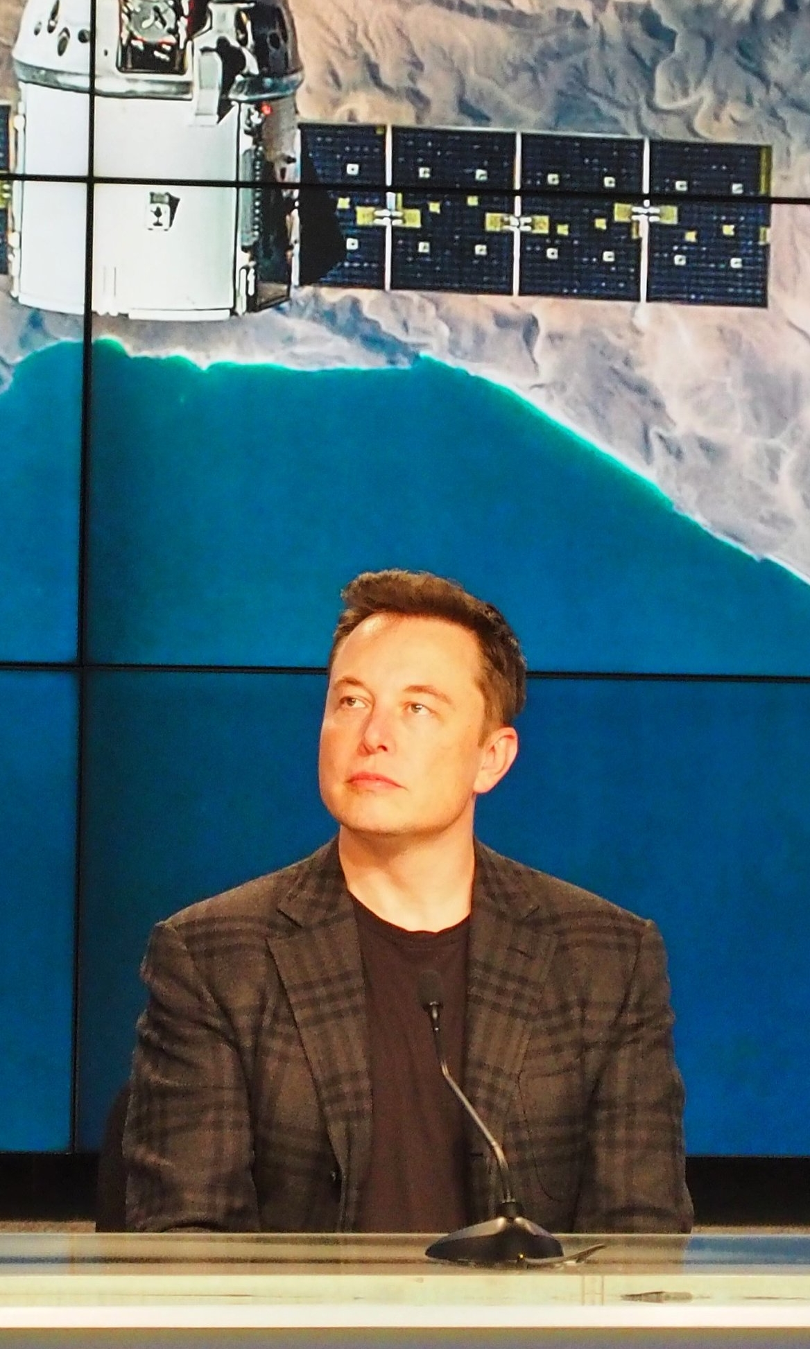 Elon Musk watches a replay of CRS-8's successful landing,at a post-launch press briefing April 8, 2015. Photo credit: theOrbital.space/Josh Dinner