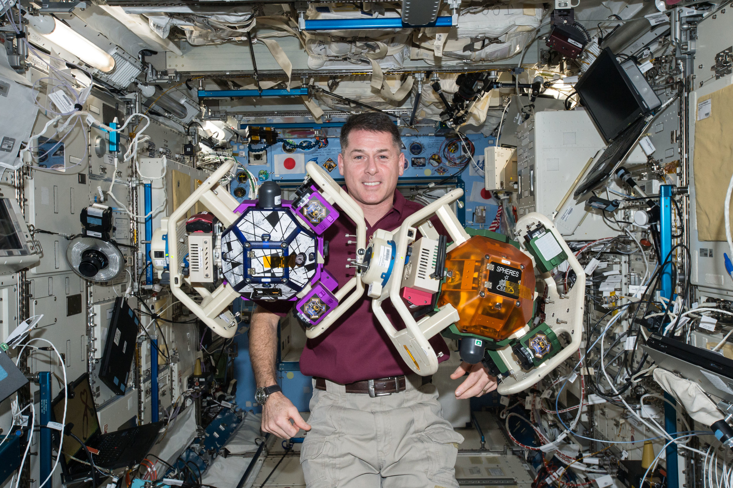 NASA Astronaut Shane Kimbrough floats inside the Destiny module with the SPHERES experiment aboard the ISS. Photo credit: NASA