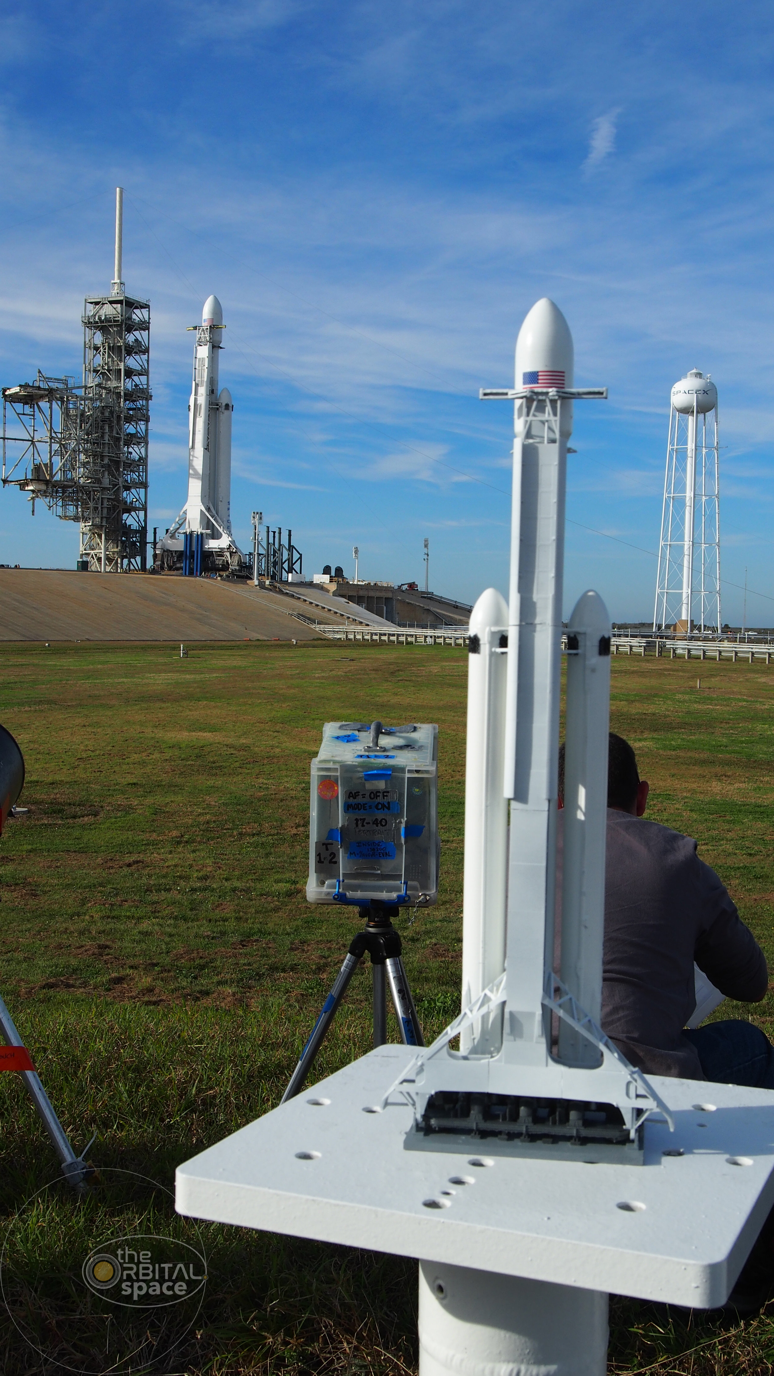 A model of SpaceX's Falcon Heavy seen with the real thing at LC-39A