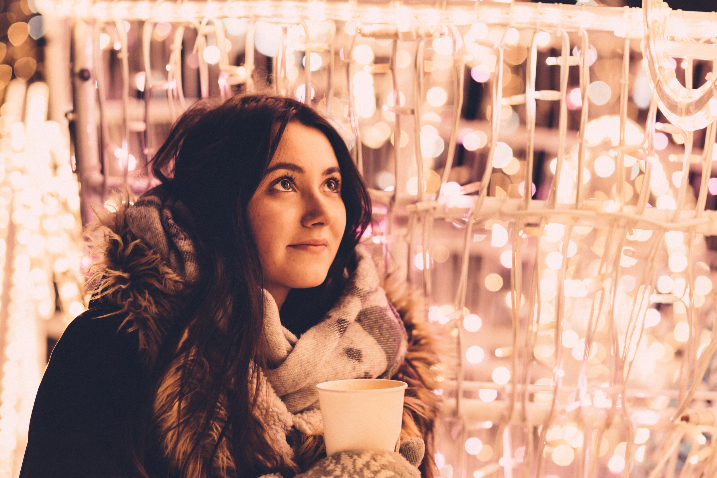 christmas_lights_and_girl_holding_coffee.jpg