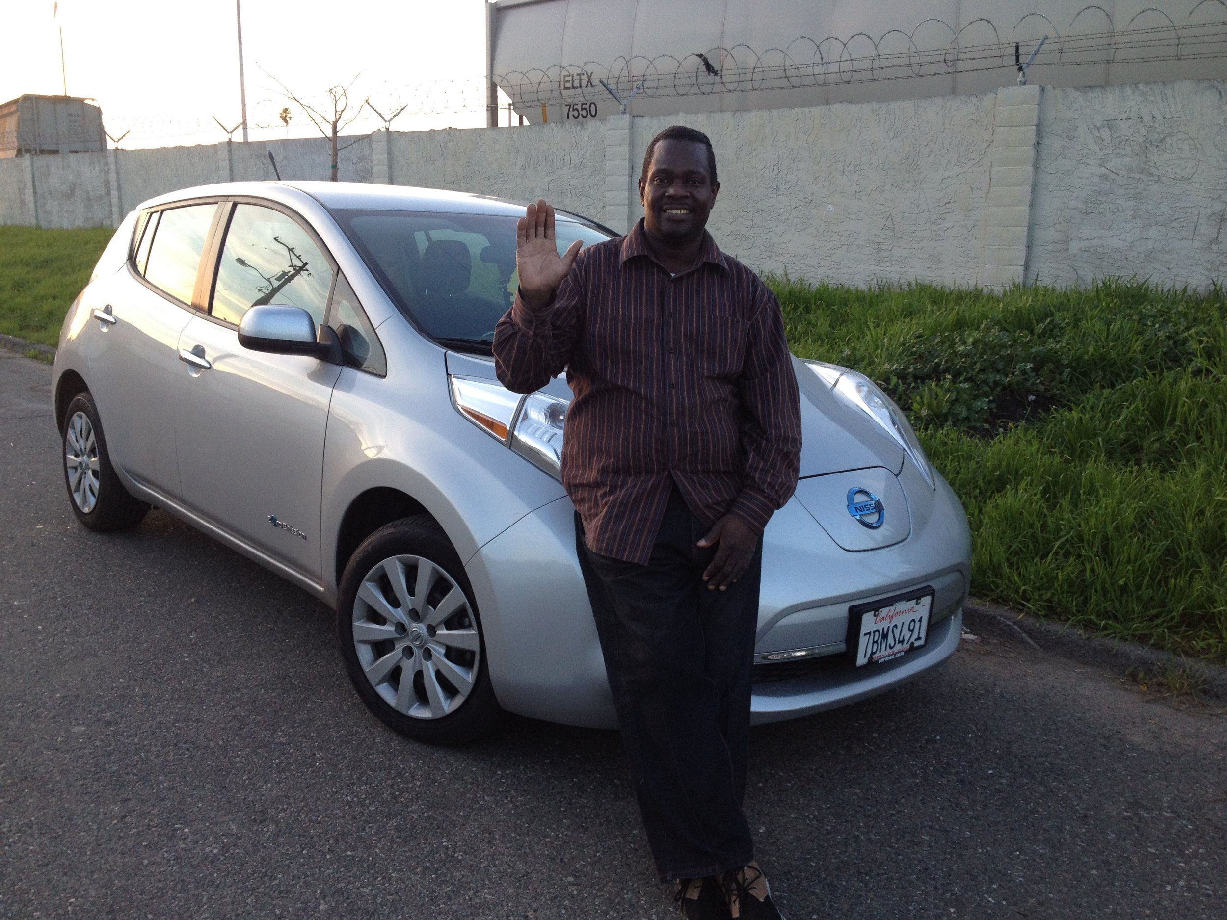 EFMP participant Jerome Mayfield stands next to his pre-owned clean car