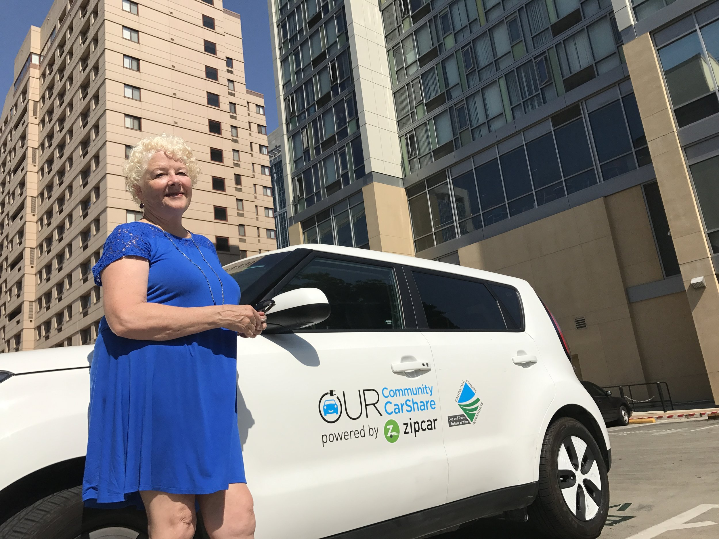 Susan Brown with an Our Community CarShare electric Kia Soul