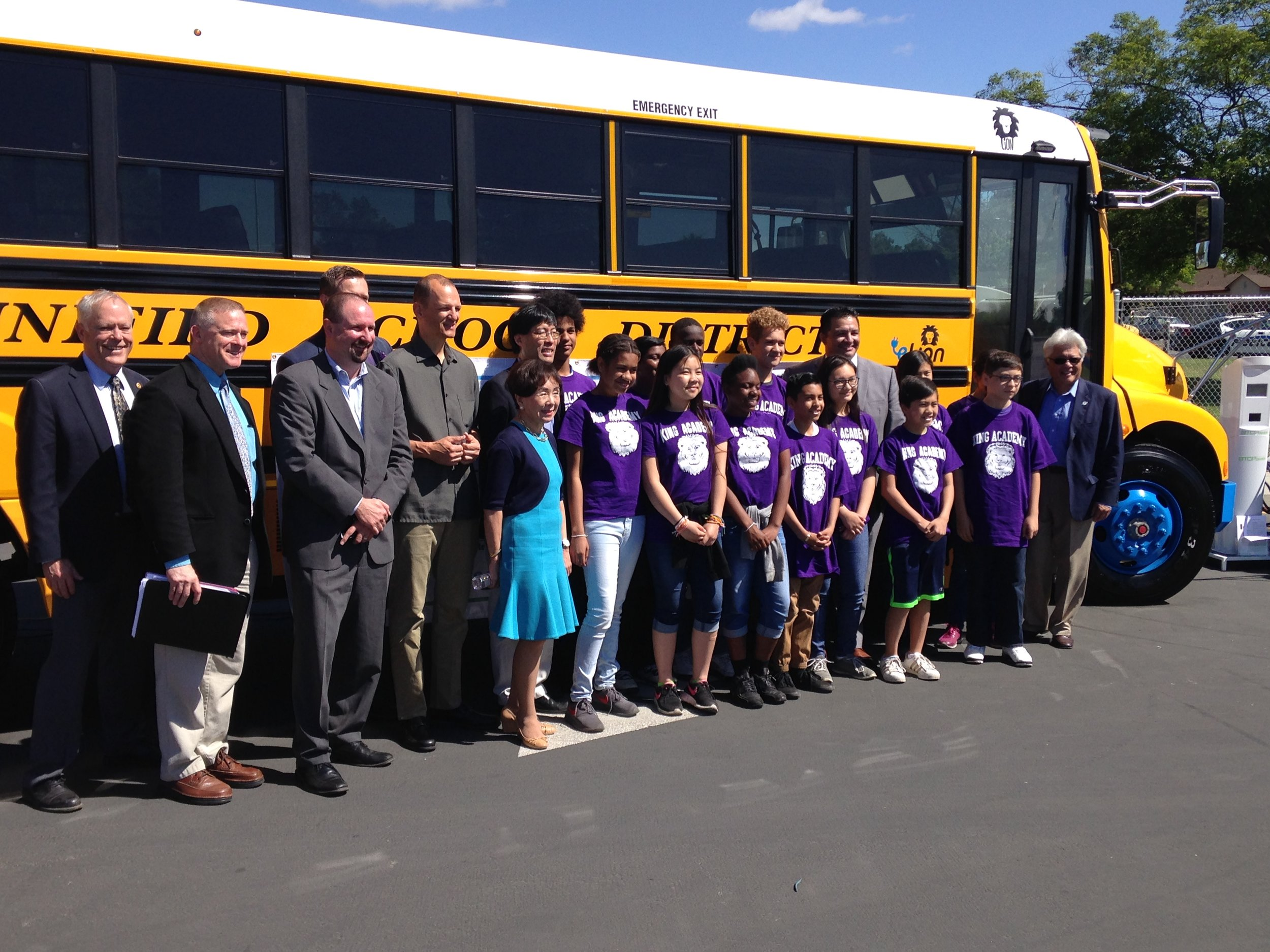 School children and administrators with electric bus
