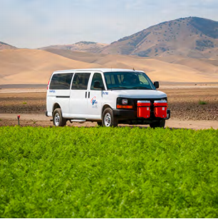 agriculture worker vanpools in san joaquin, california climate investments. image depicts a white van, with orange water containers attached to the front, driving down a dirt road.