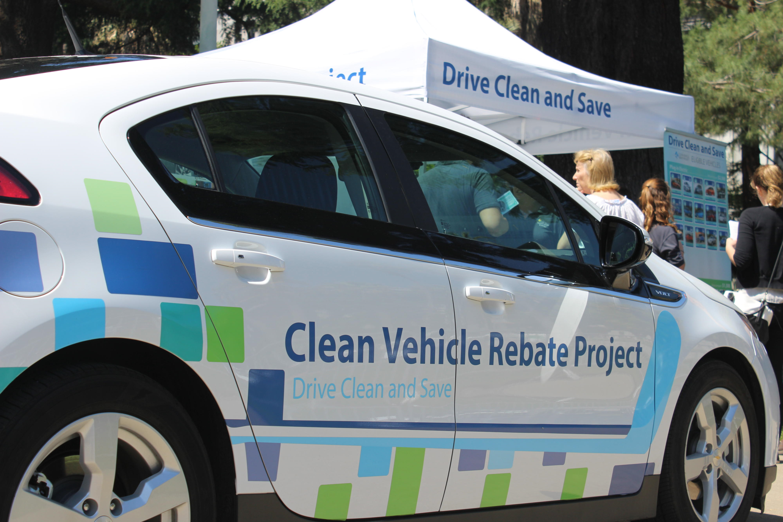 Clean vehicle rebate project, california climate investments. the image depicts a white car with the words, clean car vehicle rebate project, drive clean and save, written on it.