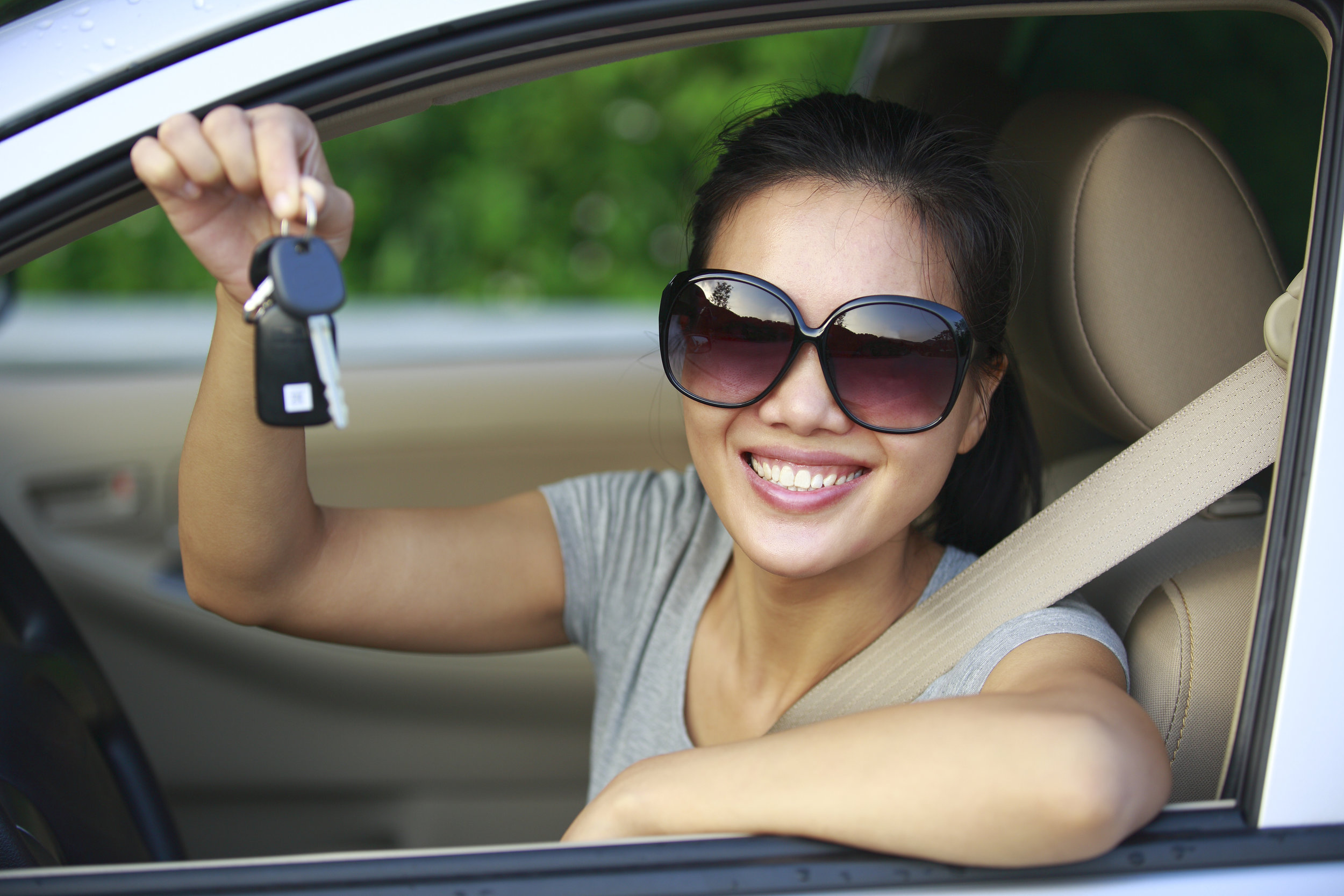 Vehicle financing assistance for lower-income consumers, california climate investments.the image depicts a woman smiling and holding a set of car keys.