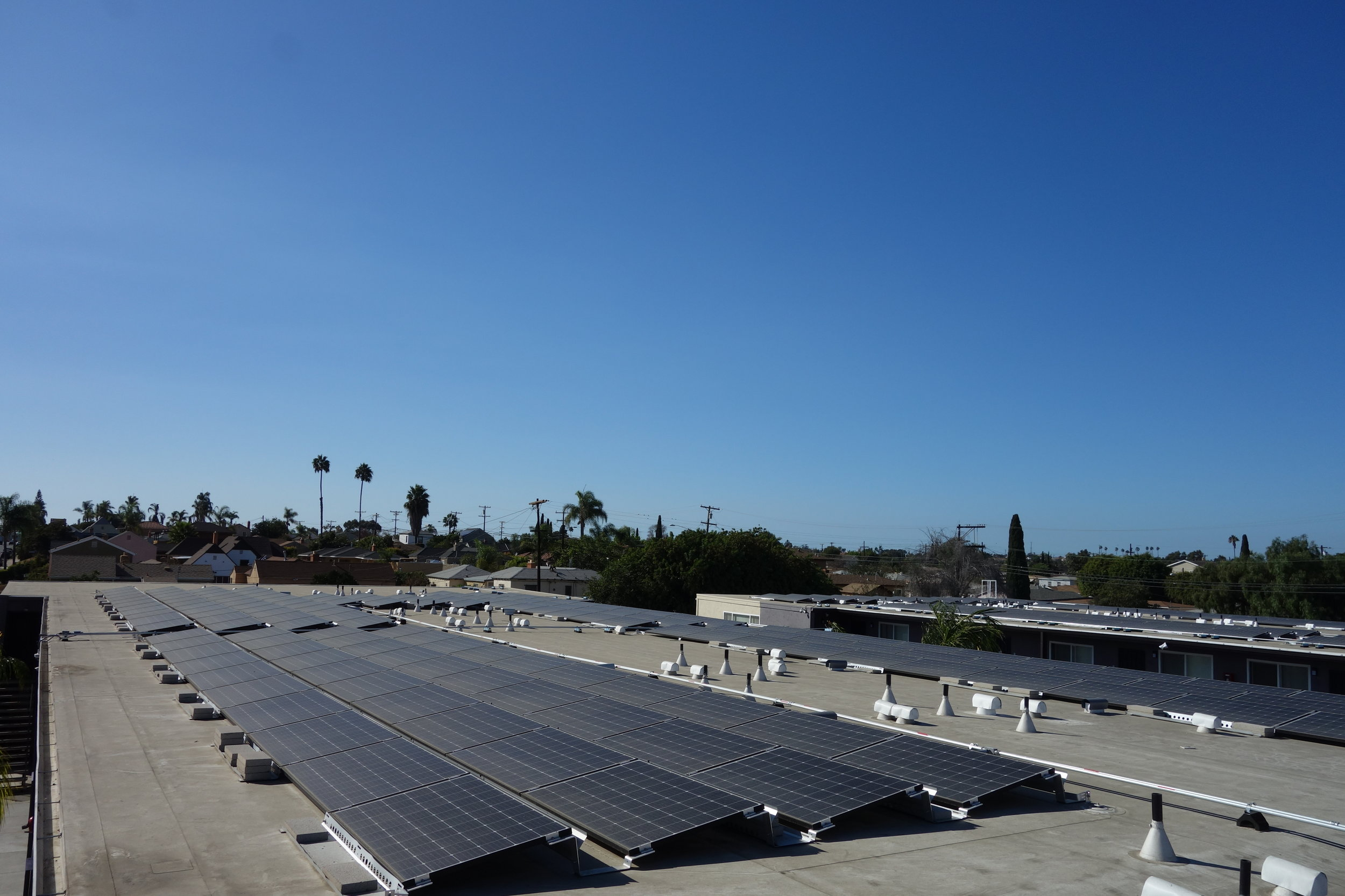 Multi-family energy efficiency and renewables, low income weatherization, california climate investments. image depicts a man on a roof, working on solar panels.