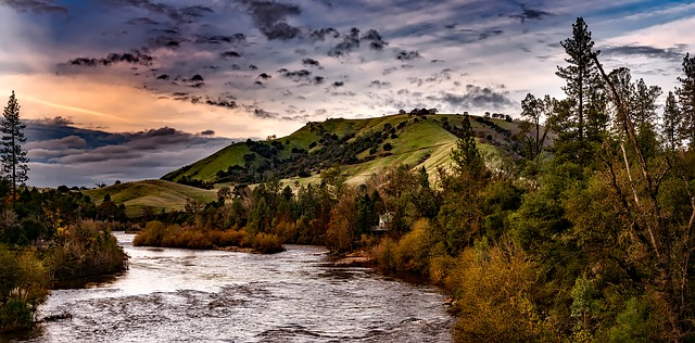 Climate adaption and Conservation easements, california climate investments. image depicts a river, trees and green hills.
