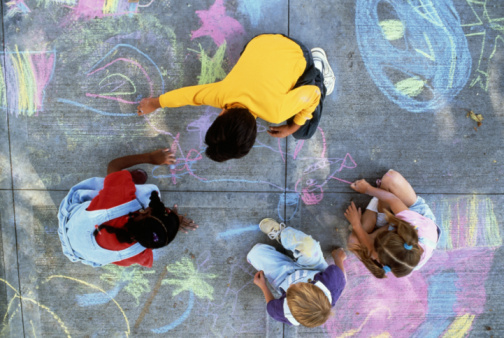 four kids drawing with chalk overhead view.jpg