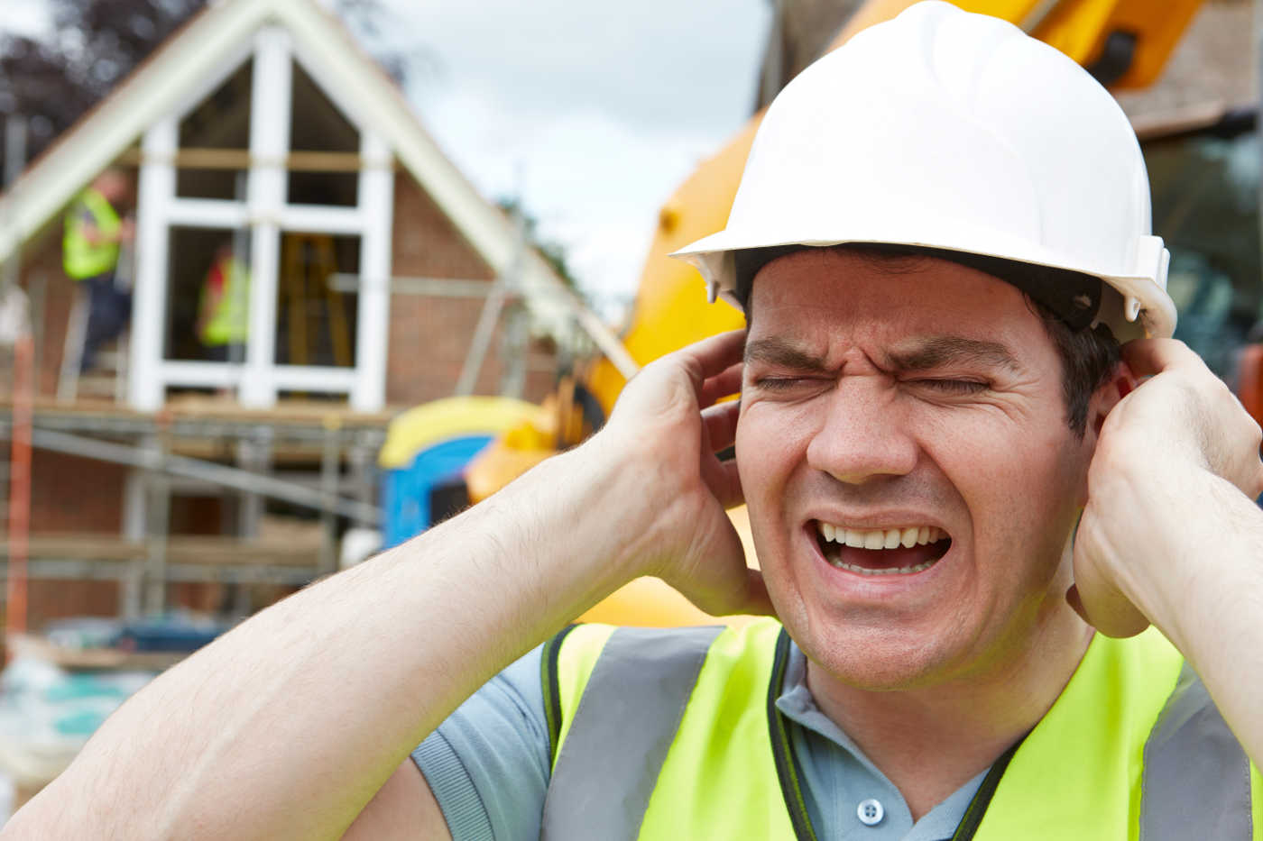 Construction Worker covering his ears and wincing in pain.