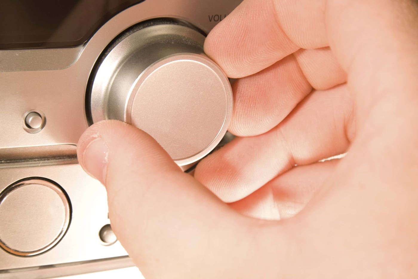 Hand adjusting the volume on a home stereo