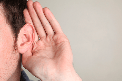 Closeup shot of a man holding his hand to his ear