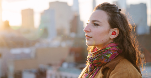 A young city dweller using a hearing aid