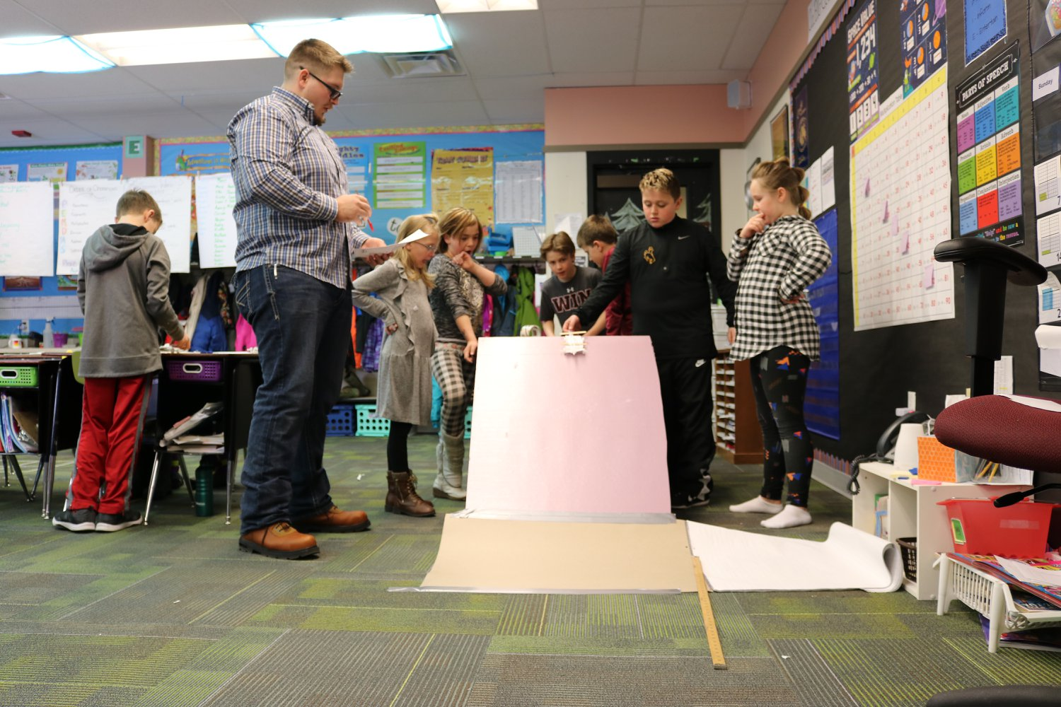 """The kids test their """"cars"""" and determine how different variables affect how far they travel down the ramp."""