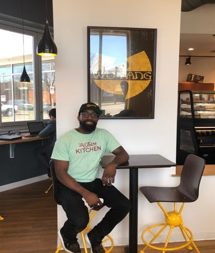 Manaan Sabir, Owner of Shindig Coffee, posing in front of the Wu-Tang poster.