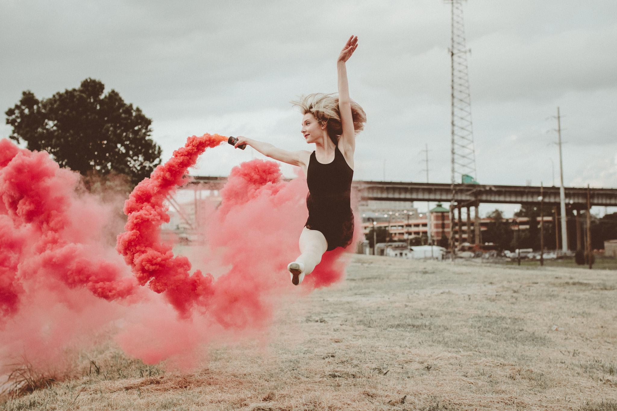 Modern, urban, lifestyle portrait of a ballerina with a smoke grenade. Downtown Baton Rouge, Louisiana