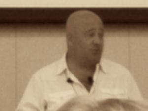 Andrew Zimmern speaking, sepia