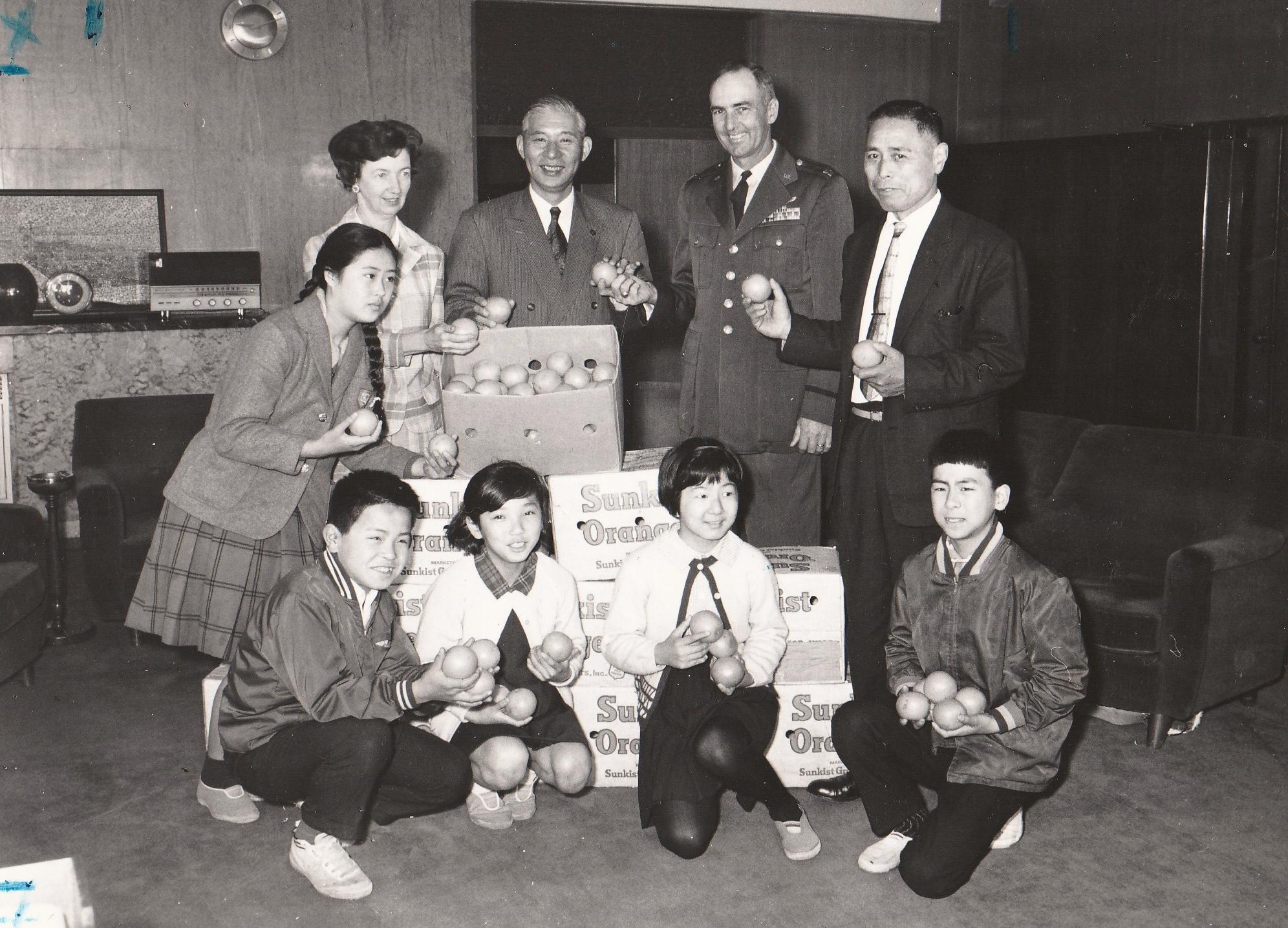 Japanese students and Tachikawa's Mayor Sakurai receiving naval oranges from   Mignon and Seymour Schweitzer.