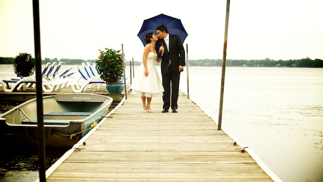 yvonne and michael holding umbrella on docks